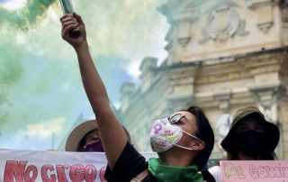 masked woman in the Plaza de niñas in Guatemala lifts up a green colourful gas fuse during a protest.
