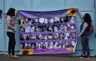 Two women hold up a purple banner filled with the faces of girls killed in the Hogar Seguro Fire