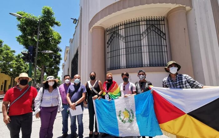 A group of individuals stand in the sun in front of a building in Guatemala holding the Guatemalan flag and a flag with a white, red, black and yellow side.